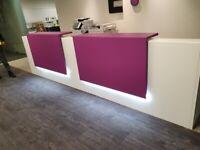 White modern office reception desk with illuminated purple panels
