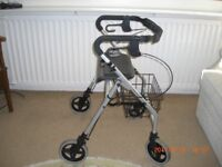 4 WHEELED MOBILITY AID WITH SEAT AND BASKET AND FOLDS UP.