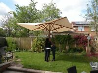 Large solid wood parasol, 3.3m diameter, used once. Caution large shaft dia to go inti table.