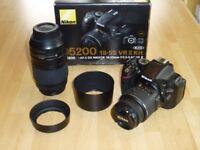 Nikon D5200 DSLR camera with two Nikkor zoom lenses