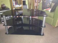 Black glass and silver television table. In excellent condition. No chips or scratches.