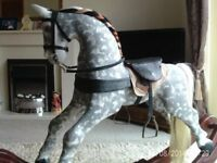 Hand carved solid wood rocking horse. Dapple grey. Leather saddle. Immaculate. Cradle type movement.