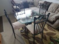 Iron glass dining table with four matching chairs.