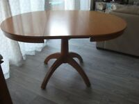 Circular dining room table extending to an oval.
