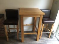 Tall solid oak kitchen table and two oak and leather seats