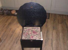 A vintage wooden sewing box painted matt black.