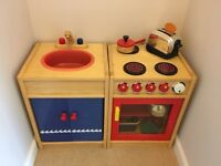 Wooden play kitchen with some play food and utensils