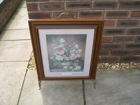 A wood framed fire screen with a glazed flower print.