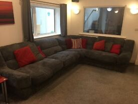 Large grey fabric corner sofa with footstool