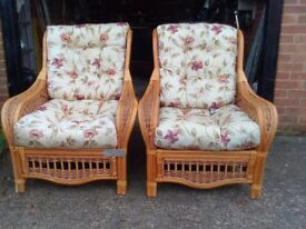 2 cane armchairs with cushions.