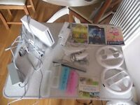 White nintendo Wii console with x2 controllers , x2 nunchucks, x2 wheels and games