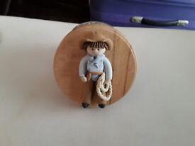 Handmade ceramic figures on wooden plaques