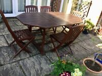Wooden extending table and five chairs.