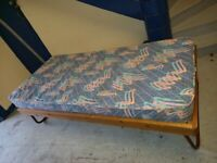 wood framed single bed with mattress and metal fold up legs