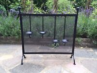 Black fire screen with 4 hanging candle stick holders on it