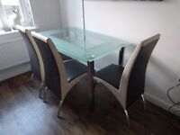 Modern glass table with lower shelf with 3 black & cream faux leather chairs.