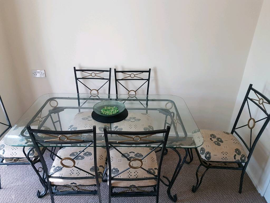 Large glass and metal dining table with 6 chairs in Stoke on
