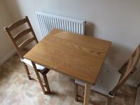 Small wooden dining table and two chairs with cushions. Size c. 1m x 1m. Used, but in good condition