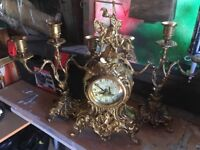 Soiled brass clock and candle holders