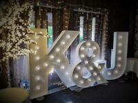 Wedding and event venue decor including large 5ft LED love letters, chair covers and centrepieces
