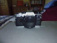Olympus OM10 SLR camera body with manual adapter.