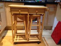 Compact wooden fold out table with stools and drawers