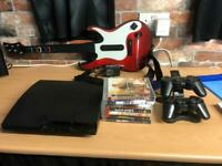Sony PS3 Slim with 7x games, 2x controllers and charging dock plus guitar