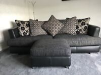 Black and silver fabric part leather suite. Consists of a 4 and 3 seater with large pouffe