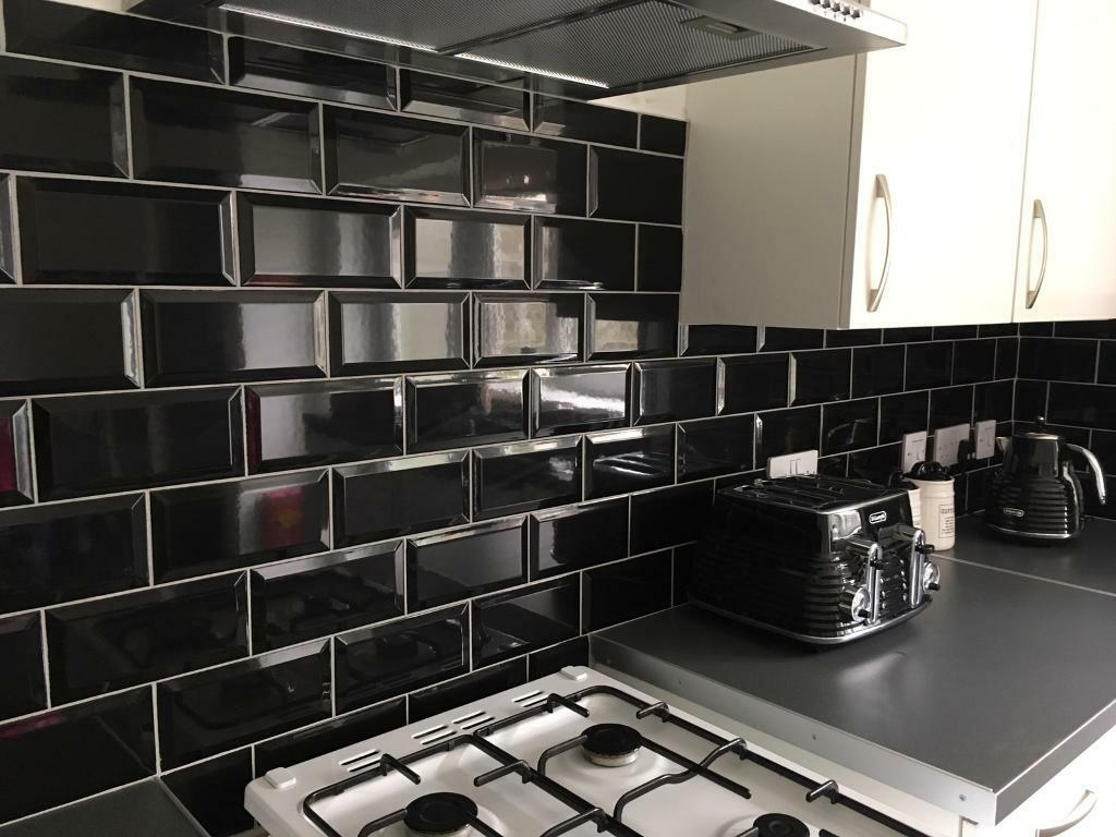 Top Almost 3 boxes of black shiny brick tiles &a half a bag of grey  GM45