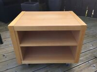Television storage cube with shelf and on wheels. In good condition.