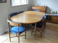 Teak extendable dining room table in good condition with eight matching chairs