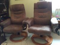 Two reclining suedette armchairs with matching footstools