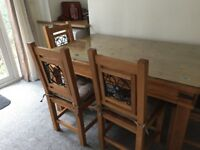 Solid pine dining table with 4 chairs and glass top. Cast iron detail. Very good condition