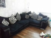 good condition black fabric corner couch with scattered cushions