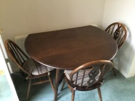 Ercol dark wood dining room table and four chairs