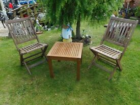 two wooden folding patio garden chairs and low wooden table