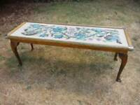 Antique style coffee table with floral tapestry glass top.