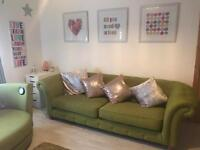Bright green chesterfield style cloth couch and cuddle chair with music and speaker installed .