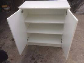 White storage cabinet with 2 shelves and doors in good condition