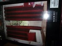 two pairs of extra long deep red curtains.