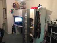 Kids high bed with wardrobe and desk below.