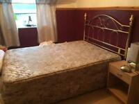Double bed with mattress and headboard.