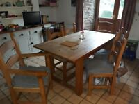 Pine dinning table and six chairs, rush seats, includes 2 carvers