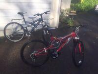 Pair of dual suspension mountain bikes.
