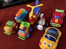 Toy cars, trucks and helicopter