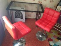 Glass table and 2 red chairs
