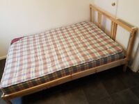 Wooden double bed with mattress.