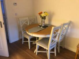 Harvey's solid oak extendable dining table and 6 chairs