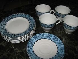A set of four cups and saucers with matching tea plates blue and gold