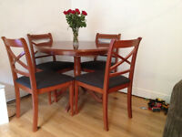 Circular Yew Table and four chairs, recently recovered in dark charcoal fabric.